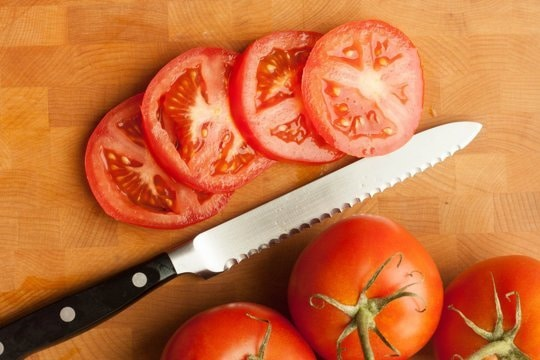 This score will act as a snip and help you to tear the rest of the skin apart. Using the score, dip your knife down into the flesh of the tomato and work your way through, this will cut the flesh easily and tear the skin from the inside out.